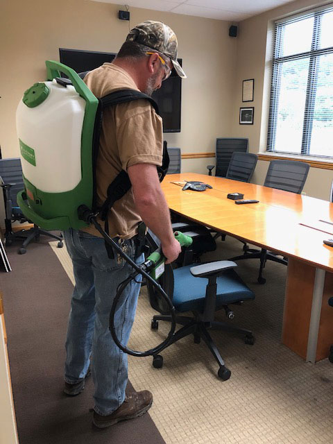 ORAU Custodian Shannon Prater using an innovative electrostatic spraying system to sanitize and disinfect ORAU facilities