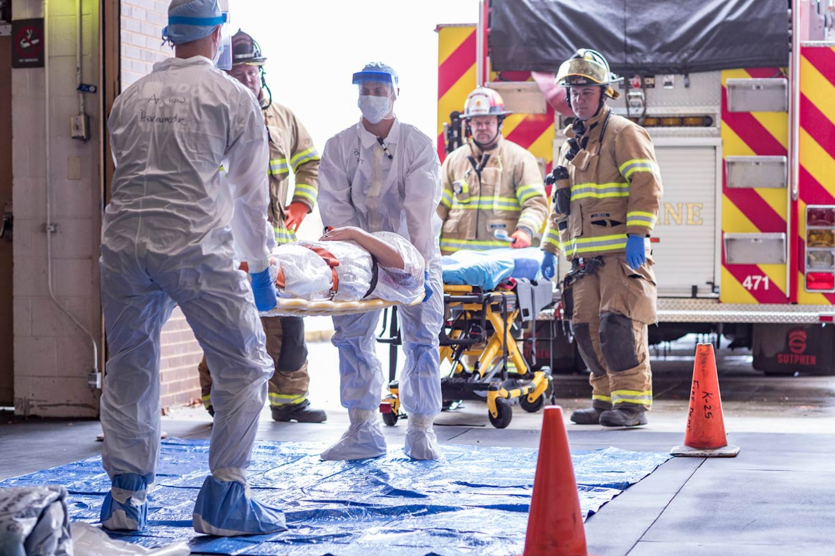 Firemen and medical staff assist patient in emergency drill