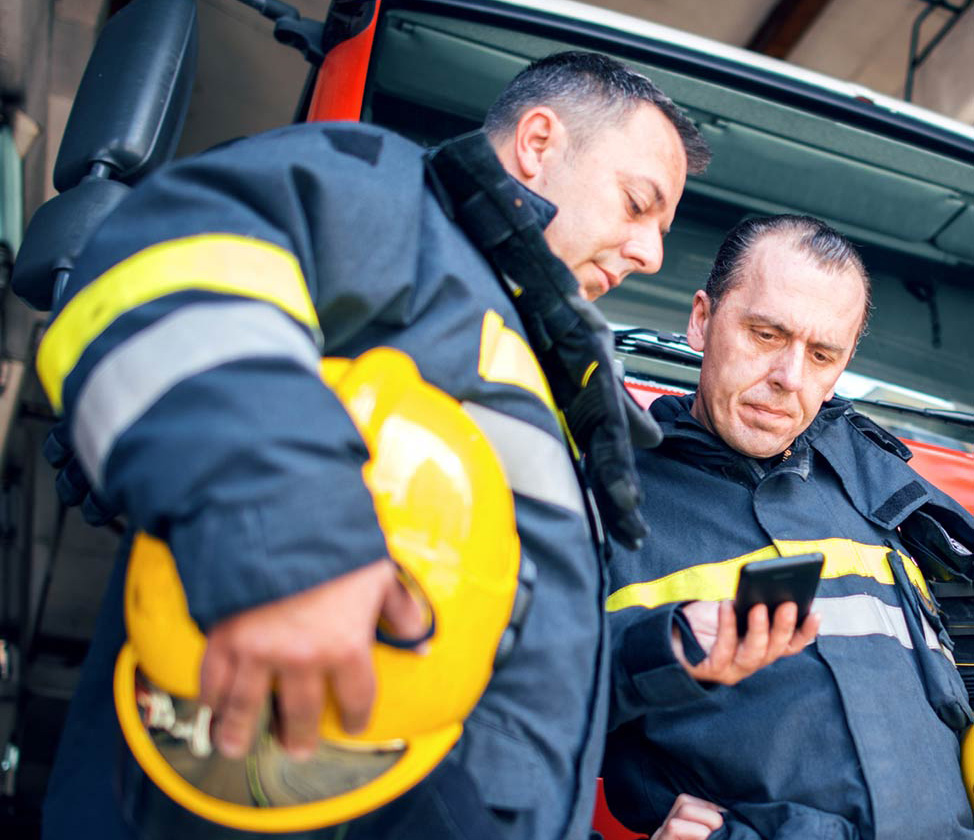 firemen looking at a smartphone screen